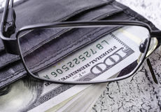 Dollars dans le portefeuille noir par des verres Photographie stock