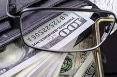 Dollars dans le portefeuille noir par des verres Photo libre de droits