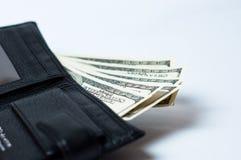 Dollars dans le portefeuille noir sur le blanc Images stock