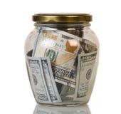 Dollars de billets de banque cent de valeur nominale dans le pot en verre d'isolement Photo libre de droits