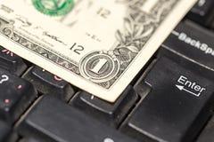 Dollars de billets de banque sur le clavier d'ordinateur portable Photos stock