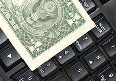 Dollars de billets de banque sur le clavier d'ordinateur portable Image stock