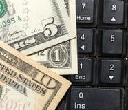 Dollars de billets de banque sur le clavier d'ordinateur portable Image libre de droits