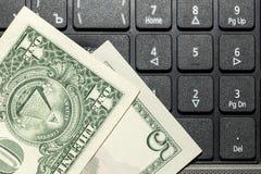 Dollars de billets de banque sur le clavier d'ordinateur portable Photographie stock libre de droits