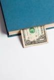 Dollars in de boeken, op witte achtergrond, bedrijfstra worden geïsoleerd die Stock Foto