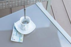 Dollars de Hong Kong et tasse de café vide sur une table en verre de café extérieur Paiement, astuce photo stock