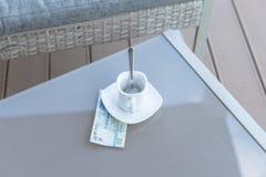 Dollars de Hong Kong et tasse de café vide sur une table en verre de café extérieur Paiement, astuce photographie stock libre de droits