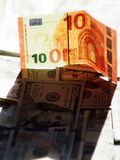 Dollars in de schaduw van de Euro door de zon wordt verlicht die royalty-vrije stock foto