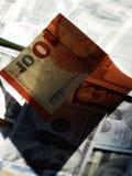 Dollars in de schaduw van de Euro door de zon wordt verlicht die Stock Afbeelding