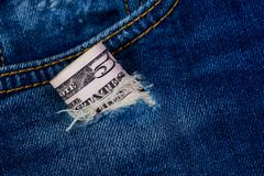 Dollars in a denim hole. Fifty dollars banknote in a hole of jeans royalty free stock images