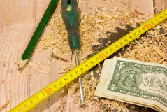 Dollars des Etats-Unis, sciure et crayon, tape-measure Image libre de droits