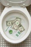 Dollars die klaar om onderaan toile worden gespoeld worden Stock Afbeeldingen