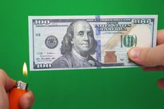 100 dollars die op een groene achtergrond branden Concept daling in economie en verlies royalty-vrije stock afbeeldingen