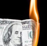 100 dollars die op een zwarte achtergrond branden Royalty-vrije Stock Afbeeldingen