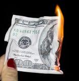 100 dollars die op een zwarte achtergrond branden Stock Fotografie