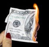 100 dollars die op een zwarte achtergrond branden Stock Foto