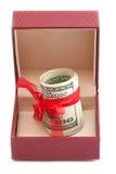 Dollars die in rode verfraaide giftdoos leggen Royalty-vrije Stock Afbeeldingen