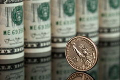 Dollars. Dollar coin standing against many dollar bills Stock Photo