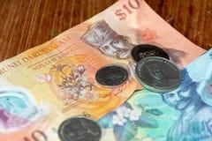 Dollars du Brunei Darussalem leur devise dans les billets et les pièces photo stock