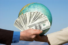 Dollars and earth. Two hands - one with dollars, another with globe stock images