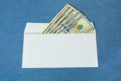 Dollars in een witte envelop stock afbeeldingen