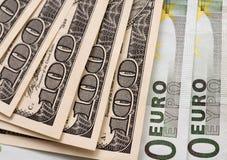 100 dollars en 100 eurobankbiljetten op Witboek Stock Foto