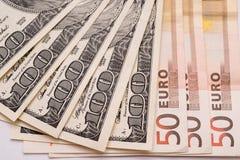 100 dollars en 50 eurobankbiljetten op Witboek Stock Foto