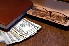 Dollars en glazen op een lijst royalty-vrije stock afbeelding