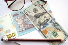 100 dollars en hryvnia 100, glazen en een potlood Bedrijfs concept stock fotografie