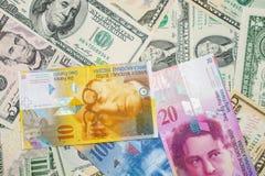 Dollars en Zwitserse franken Stock Afbeeldingen