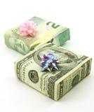 Dollars enroulés autour de deux cadeaux avec des proues images libres de droits