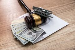 Dollars in an envelope, handcuffs and hammer judges. The concept of corruption - dollars in an envelope, handcuffs and hammer judges royalty free stock photography
