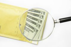 Dollars in the envelope with magnifying glass Stock Images