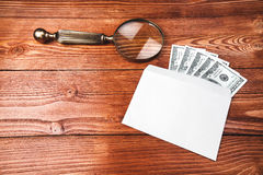 Dollars in an envelope with magnifying glass. Five hundred dollars out of one hundred dollar bills in an envelope with vintage magnifying glass lying on wooden Royalty Free Stock Photography