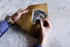 Dollars in an envelope in man hands. stock photos