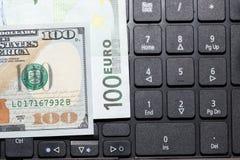 Dollars et euros sur un clavier d'ordinateur portable Image libre de droits