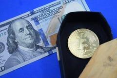 Dollars et mensonges de bitcoin de pièce de monnaie dans un cercueil Photo stock