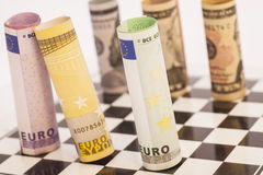 Dollars and Euro banknotes on chess board Stock Photos