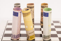Dollars and Euro banknotes on chess board Royalty Free Stock Image