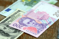 Dollars euro and hryvnia banknotes on wooden background Stock Photography