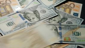 Dollars and euros are falling on the table. stock footage