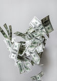 Dollars are falling. Dollars bills are falling. Money is flying in the air. Dollars fly on gray background. Fake money. Business concept. Shallow depth of field Royalty Free Stock Images