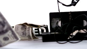 Dollars falling beside film video tapes and closed sign. In slow motion stock video