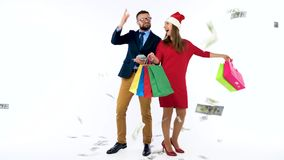 Dollars falling on formally dressed man and woman in the Santa Claus hat. Let`s go holiday shopping and celebrate. Dollar bills falling on formally dressed man stock video