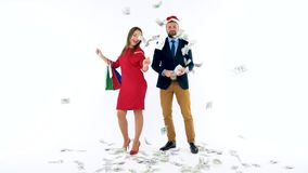 Dollars falling on formally dressed man and woman in the Santa Claus hat. Let`s go holiday shopping and celebrate. Dollar bills falling on formally dressed man stock video footage