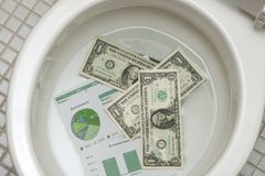 Dollars getting ready to be flushed down the toile Stock Photos