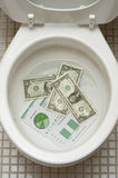 Dollars getting ready to be flushed down the toile. T. Photo for  payments, finance, taxes, wasteful spending and any other financial inference Stock Images
