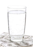 Dollars and glass of water Stock Photos