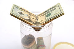 Dollars going into a jar money, Saving concept Stock Image