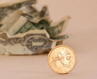 Dollars and golden coin. Crumpled dollars and golden coin Stock Images